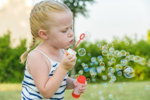 Sympathetically playing girl and her soap bubbles